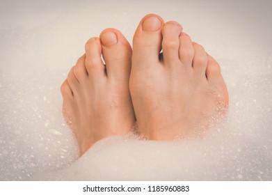 Beautiful female feet in bathtub with foam - retro style