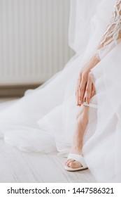 Beautiful female feet closeup. Bride dresses shoes before the wedding ceremony. Wedding bride shoes.