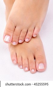 Beautiful female feet with the French pedicure on a white towel