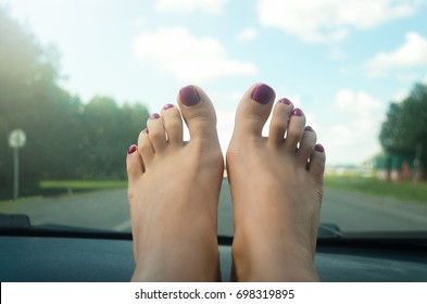 Beautiful female feet on the dashboard of the car. Travel or relaxation concept.