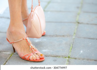 beautiful female feet with pedicure in sandals and a small handbag. with copy space. small depth sharpness