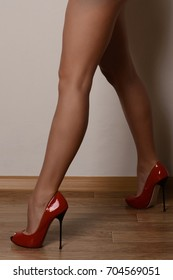 beautiful female feet in red high-heeled shoes.