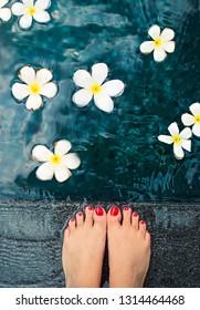 Beautiful female feet in swimming pool with white frangipani flowers