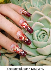 Beautiful female fingers with nice abstract foil nail art design manicure on an exotic flower