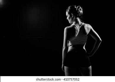 Beautiful female fitness model holding her towel/weights in a dark studio while covered in sweat after her training.