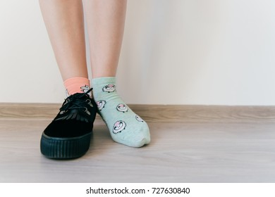 Beautiful female foot in sock. Other women`s leg in black suede shoe with tankette. Weird strange kinky odd bizarre concept. Inattentive eccentric mismatched clothes. Different pair of socks.