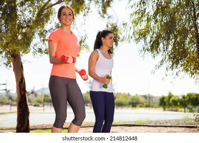 Beautiful female friends working out and walking with dumbbells outdoors