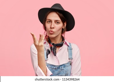 Beautiful female gestures as shows real taste of Italian pasta, didn`t eat something more delicious, dressed in casual denim dungarees, black hat, isolated over pink background. Mmm, that`s wonderful!