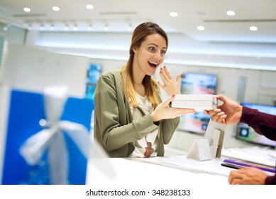 Beautiful female getting present at shop. She is taking present with one hand and laughing, covering her mouth with hand. Shallow depth of field.
