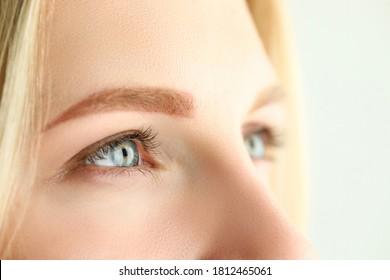 Schöne grün-graue und graue Augen, die irgendwo in die Ferne schauen, Nahaufnahme