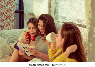 Beautiful female group three friends happily enjoy on sofa with fun in living room at home with bright smile morning,with warm sunshine, concept relaxation and refreshment,vintage style
