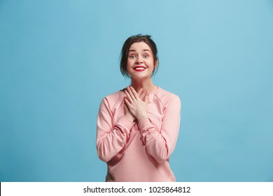 Beautiful female half-length portrait isolated on blue studio backgroud. The young emotional smiling and surprised woman standing and looking at camera.The human emotions, facial expression concept