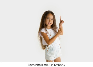 Beautiful female half-length portrait isolated on white studio background. Little emotional asian girl wearing white. Facial expression, human emotions, advertising concept. Pointing up.