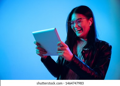 Beautiful female half-length portrait isolated on blue studio background in neon light. Young emotional woman. Human emotions, facial expression concept. Using tablet for talking or internet serfing.