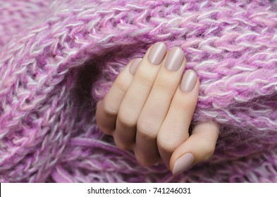 Beautiful female hand with beige manicure holding pink scarf.