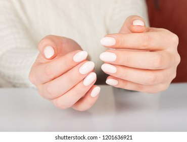 Beautiful female hand with beige nail design.