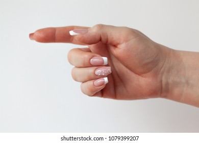 The beautiful female hand with graceful French manicure shows the sign of a direction