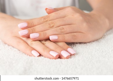 Beautiful female hand with light pink nail design.