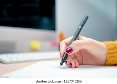 Beautiful female hand with manicure writing on a white paper at the office. Morning at a creative studio. Graphic design, mock up screens. glasses, pens, keyboard, notebook, colors, modern, laptop