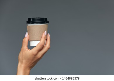 A beautiful female hand offers a hot drink, tea or coffee in a disposable natural glass on a light gray background. CONCEPT start of the day with a cup of coffee