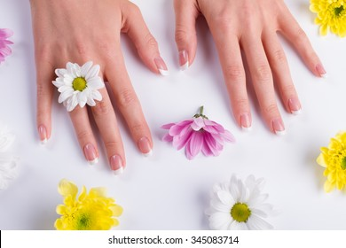 Beautiful female hands among the flowers. Gentle spring manicure.