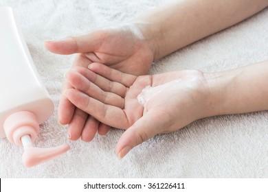 Beautiful female hands applying hand cream