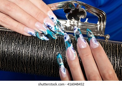 Beautiful female hands with blue flower manicure holding the black handbag.