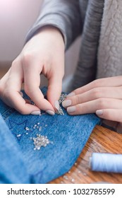 Beautiful female hands embroider with beads stars on denim. Lens flare from the corner.
