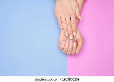 Beautiful Female Hands with French manicure over colorful paper background