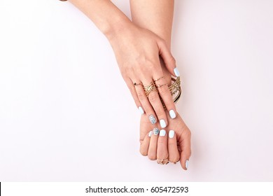 Beautiful female hands in gold bracelets and rings. Fashionable female manicure on white background.