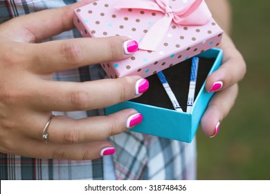 Beautiful female hands hold the box in which lie pregnancy tests