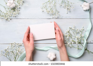 Beautiful female hands holding empty paper card with blank space on light blue wooden desk with flowers. Tender greeting card composition for womens or mothers day, easter, spring holidays.