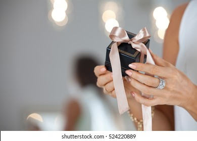 Beautiful female hands holding a small gift box. Holidays and celebration concept.