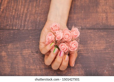Beautiful female hands with modern manicure and pink flowers on a mahogany background with tint