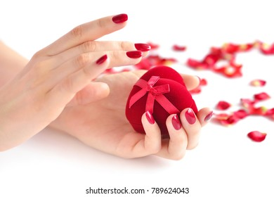 Beautiful female hands with red manicure holding a box of heart-shaped. Happy Valentines day, love concept.