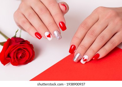 Beautiful female hands with romantic manicure nails, hearts and Valentine's day design