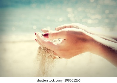Beautiful female hands and the sand on the sea background