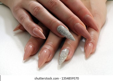 Beautiful female hands with sharp nails manicure. Beautiful sharp long nails, extensions, gel polish. Long sharp pink shiny and crystal nails.