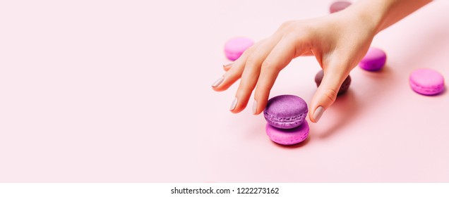 Beautiful female hands with trendy manicure holding pink macaroon cake. Creative Top view of hands and tasty cakes, flat lay. Copyspace for your text.