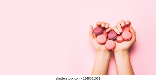 Beautiful female hands with trendy manicure holding pink macaroon cake. Top view, flat lay. Copyspace for your text.