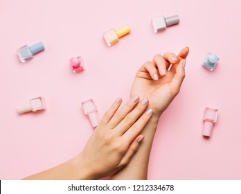 Beautiful female hands with trendy stylish manicure on pink background. Multicolored Bottles of nail polish. Top view, flat lay.
