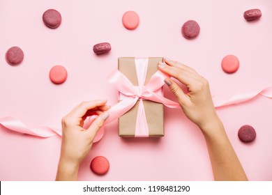 Beautiful female hands vith fashion manicure tie a bow on gift box on pink table vith macaroons around. Top view, flat lay. Party and holiday concept.