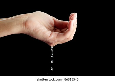 Beautiful female hands with water isolated on black background