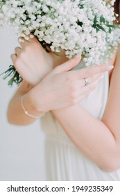 Beautiful female hands and wedding bridal bouquet in fineart style