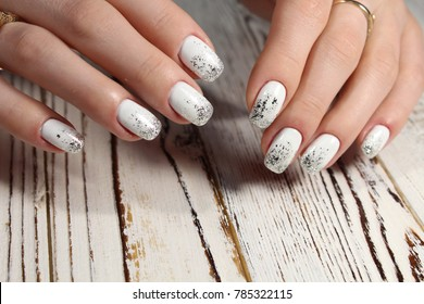 beautiful female hands with white nails on a wooden table