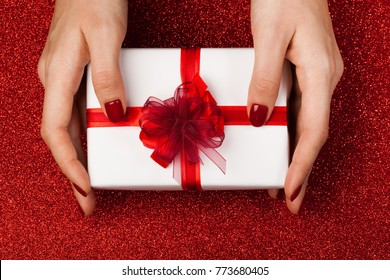 Beautiful female hands with a wrapped present on a brilliant festive red background. Perfect manicure. Concept of the New Year, Christmas, Valentine's Day, gifts