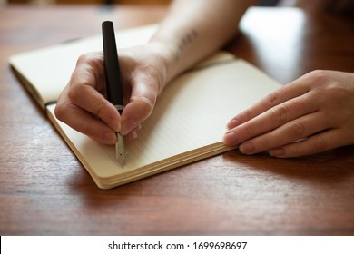 Beautiful female hands writing a journal entry in a diary using an ink fountain pen.