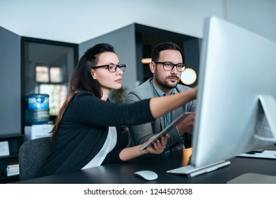 Beautiful female and handsome male office workers working together.