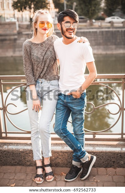 Beautiful female and handsome man  are standing near the river in the city.