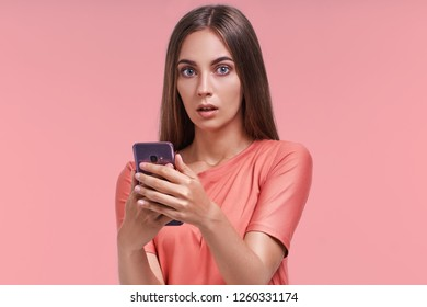 Beautiful female has attractive appealing appearance and shocked expression, received unexpected news on mobile phone, types message on modern electronic device, reads shocking promotional offer